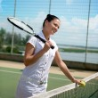 Stock Photo: Young woman on a tennis court