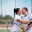 A woman and a man on the  tennis courts - Stock Photo