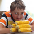 Portrait of a boy at the table with a plate of corn — Stock Photo #11670665