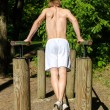 Man pull-ups on a bar in a forest. From the back. — Stock Photo #10917359