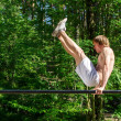 Attractive man pull-ups on a bar in a forest — Stock Photo #10917363