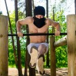 Antiglobalist trains, pull-ups on a bar in a forest — Stock Photo #10917369