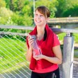Smiling female runner with bottle of water — Stock Photo