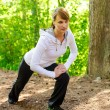 Stock Photo: Attractive young woman stretching in forest