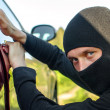 Thief in the mask breaks the door in the car - Stock Photo