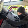 Stock Photo: Thief in the mask breaks the door in the car