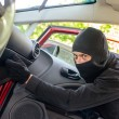 Thief in the mask breaks the door in the car — Stock Photo #10917506
