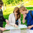 Three friends traveling, they look at a map — Stock Photo #10917533