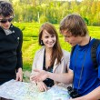 Three friends traveling, they look at a map — Stock Photo #10917540