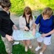 Three friends traveling, they look at a map — Stock Photo