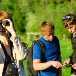 Three friends traveling. Girl looking through binoculars — Stock Photo #10917544
