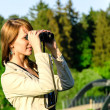Attractive young woman looking through binoculars — Stock Photo #10917553