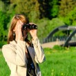 Attractive young woman looking through binoculars — Stock Photo