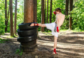 Fighter kicking rubber wheels with the leg — ストック写真
