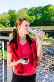 Attractive woman drinking water on the bridge — Stock Photo