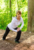 Attractive young woman stretching in forest — Stok fotoğraf