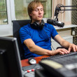 Dj working in front of a microphone on the radio — Stock Photo