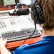 Dj working in front of a microphone on the radio, from the back — Stock Photo