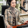 Anchorwoman sitting in front of a microphone on the radio — Stock Photo #11014232