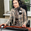 Anchorwoman sitting in front of a microphone on the radio — Stock Photo