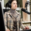 Anchorwoman sitting in front of a microphone on the radio — Stock Photo #11014266