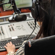 Foto de Stock  : Anchorwomsitting in front of microphone on radio, from back