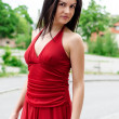Stock Photo: Beautiful girl in red dress posing on the street