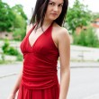 Beautiful girl in red dress posing on the street — Stock Photo