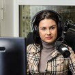 Anchorwoman in front of a microphone on the radio — Stock Photo