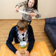 Domestic violence: Wife beating her husband with a plate — Stok fotoğraf