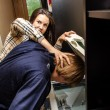 Office revenge: Woman tries to shove the man in the copy machine — Stockfoto