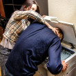 Office revenge: Woman tries to shove the man in the copy machine — Zdjęcie stockowe