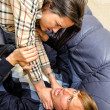 Stock fotografie: Office fight: Woman trying to stifle a man on the sofa