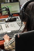 Anchorwoman sitting in front of a microphone on the radio, from the back — Stock Photo