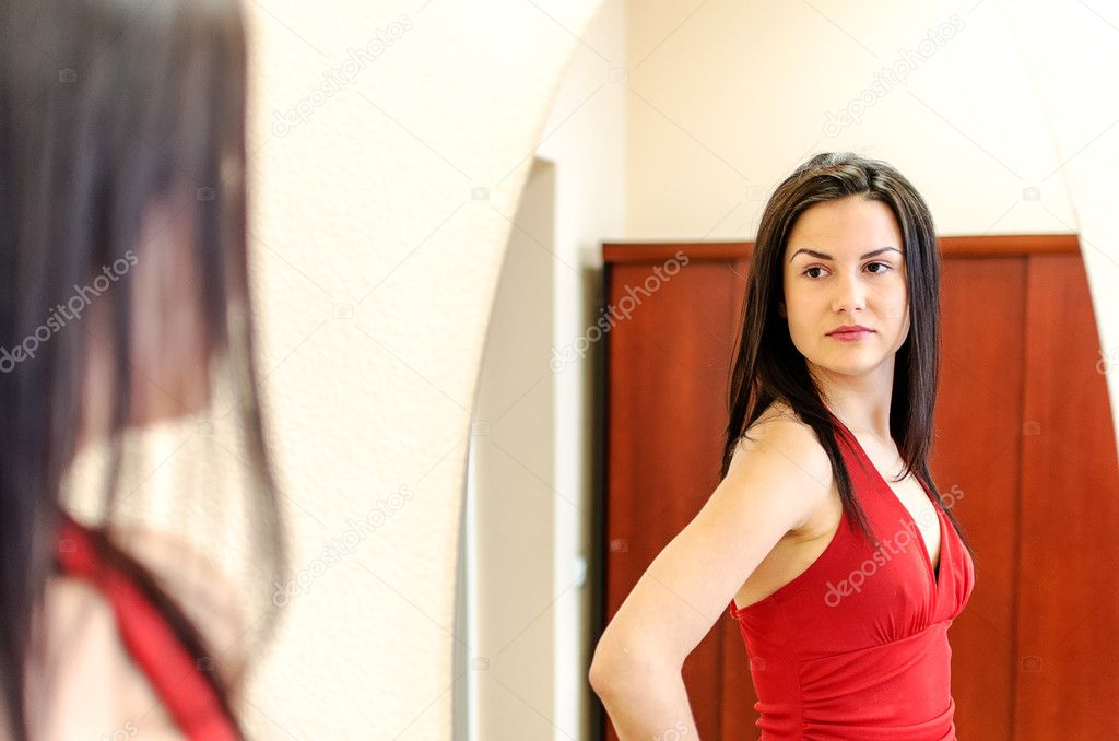 Beautiful girl in red dress posing in front of a mirror  Stock Photo #11014285