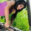 Woman repairing broken car with a socket spanner wrench. — Stock Photo #11327526