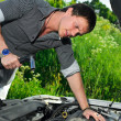Stock Photo: Young man repairing broken car with a socket spanner wrench.