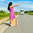 Womwith suitcase hitchhiking car — Stock Photo #11327548