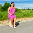 Woman sitting on suitcase on the road. — Стоковая фотография