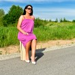 Woman sitting on suitcase on the road. — Stock Photo