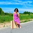 Woman with rose sitting on suitcase on the road — Stock Photo