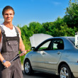 Handsome mechanic on a road near the broken car — Stock Photo