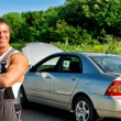 Handsome mechanic on a road near the broken car — Stock Photo #11327561
