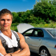 Handsome mechanic on a road near the broken car. — Stock Photo #11327566