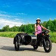 Pretty woman riding a motorcycle with a sidecar. — Stock Photo