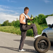 Handsome mechanic with a tire on a road — Stock Photo #11327578