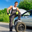 Handsome mechanic standing on a tire on the road — Stock fotografie