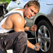 Mechanic fixing a tire on a road - Stock Photo