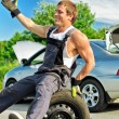 Portrait of laughing mechanic sitting on a tire on a road. — Stock Photo