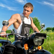 Handsome man in a boilersuit standing near motorcycle. — Stock Photo